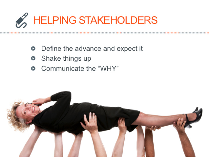 PowerPoint slide designed by Joel Mertz. There is a graphic of a crowd holding up a businesswoman who is crowd surfing. The title of the slide reads, HELPING STAKEHOLDERS.